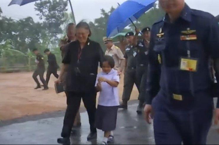 ภาพประทับใจ สมเด็จพระเทพฯทรงประคองเด็กหญิงเข้าหลบฝน